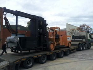 Lowloader with self loading ramps carrying big forklift